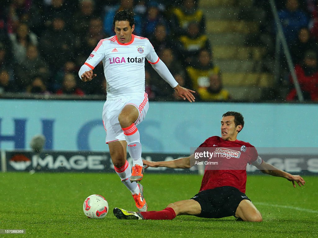 Claudio Pizarro of Muenchen is challenged by Julian Schuster of Freiburg during the Bundesliga match between SC Freiburg and FC Bayern Muenchen at MAGE SOLAR Stadium on November 28, 2012 in Freiburg im Breisgau, Germany.