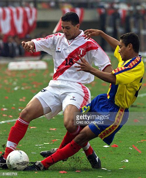 Claudio Pizarro of the Peruvian national team carries the ball as Edwin Tenorio of Ecuador lunges 02 June 2001 in a World Cup qualifying match Lima...