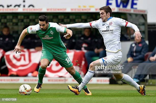 Claudio Pizarro of Werder Bremen is chased by Stefan Bell of 1 FSV Mainz 05 during the Bundesliga match between Werder Bremen and 1 FSV Mainz 05 at...
