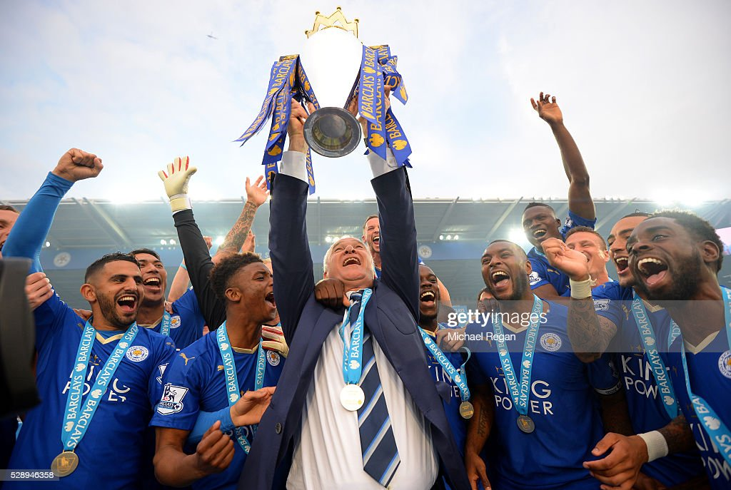 Claudio Ranieri Manager of Leicester City lifts the Premier League Trophy as players celebrate the season champions after the Barclays Premier League match between Leicester City and Everton at The King Power Stadium on May 7, 2016 in Leicester, United Kingdom.