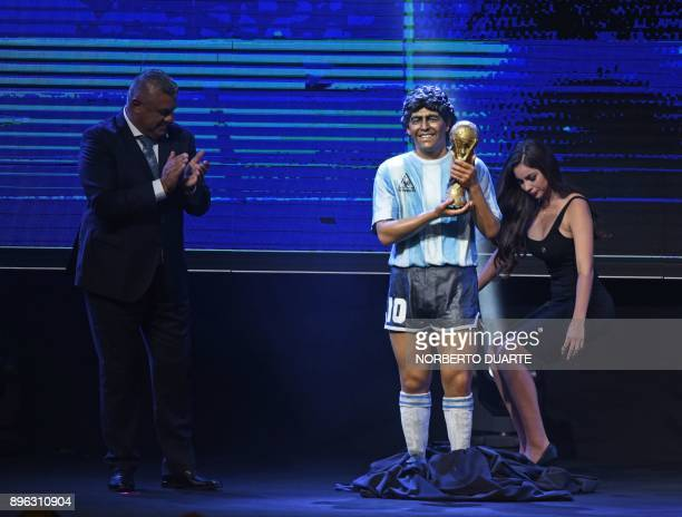 Claudio Tapia the president of the Argentine Football Association stands next to a statue of legendary Argentine footballer Diego Armando Maradona in...