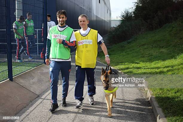 Claudio Yacob of West Bromwich Albion gives Dave Heeley a helping hand with guide dog Seamus as West Bromwich Albion celebrate the 25th anniversary...