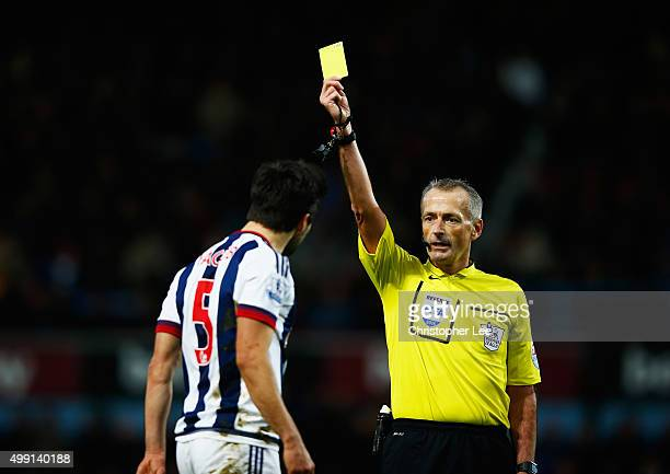 Claudio Yacob of West Bromwich Albion is shown a yellow card by referee Martin Atkinson during the Barclays Premier League match between West Ham...