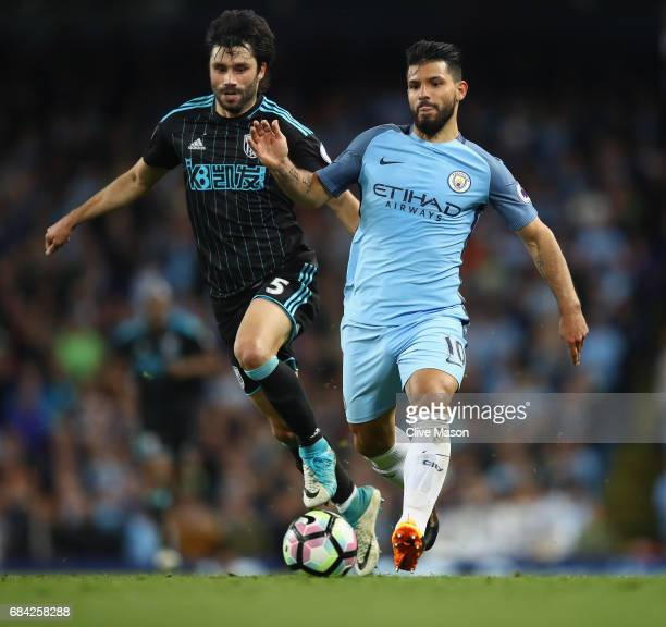 Claudio Yacob of West Bromwich Albion is tackled by Sergio Aguero of Manchester City during the Premier League match between Manchester City and West...