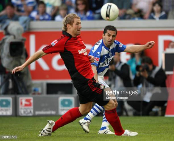 Claudiu Niculescu of Duisburg takes a shot at the goal and Lukas Sinkewicz of Leverkusen tries to block him during the Bundesliga match between MSV...