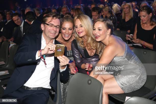 Claus Strunz Kerstin Linnartz fashion designer Sonja Kiefer and Regina Halmich watch their selfie during the 'Tribute To Bambi' gala at Station on...