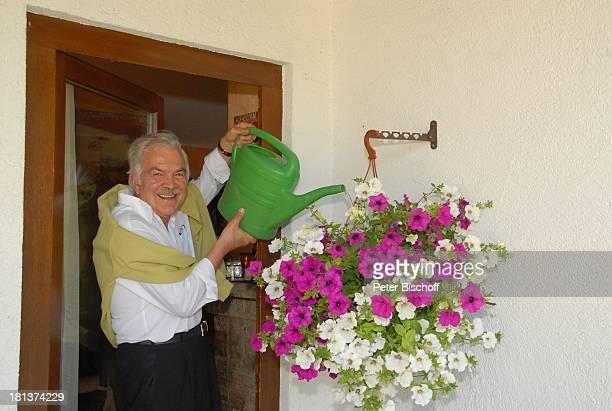 Claus Wilcke Homestory Rot am See Landkreis Schwäbisch Hall BadenWürttemberg Deutschland Europa AmpelPflanze gießen vor Haustür Gießkanne Schauspieler