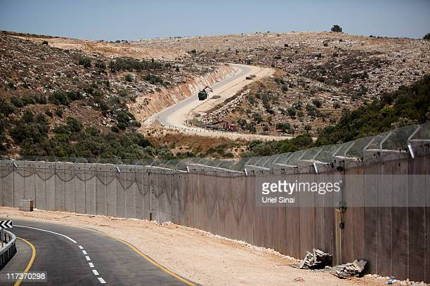 A claw excavator lifts parts of a torndown metal fence a section of the controversial Israeli barrier on June 26 2011 near the West Bank village of...