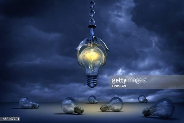 Claw grabbing illuminated light bulb