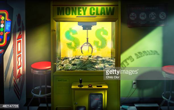 Claw grabbing money in money claw arcade machine