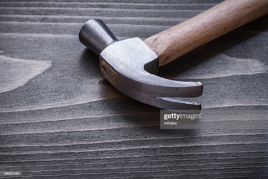 Claw hammer on vintage wood board close up construction concept : Stock Photo