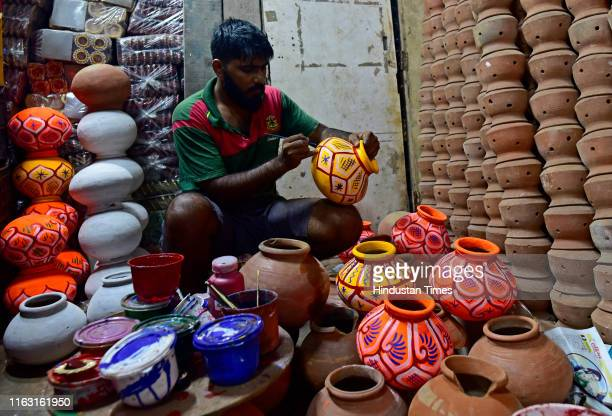 Clay arties give finishing touches to colourful pots that will be used during the Dahi Handi celebrations this Janmashtami at kumbharwada on August...