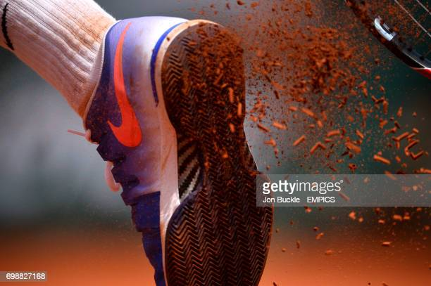 Clay breaks off the sole of the tennis shoe of Roger Federer as he serves during his Second round men's singles match against Marcel Granollers on...