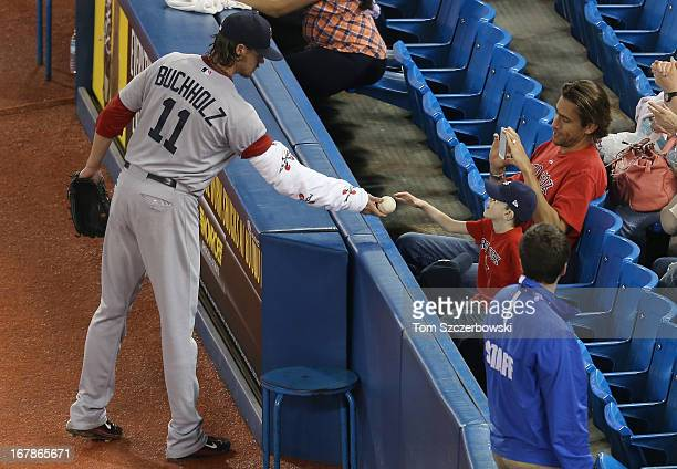 Clay Buchholz of the Boston Red Sox hand sthe baseball to a fan as he makes his way to the dugout from the bullpen before an MLB game action against...