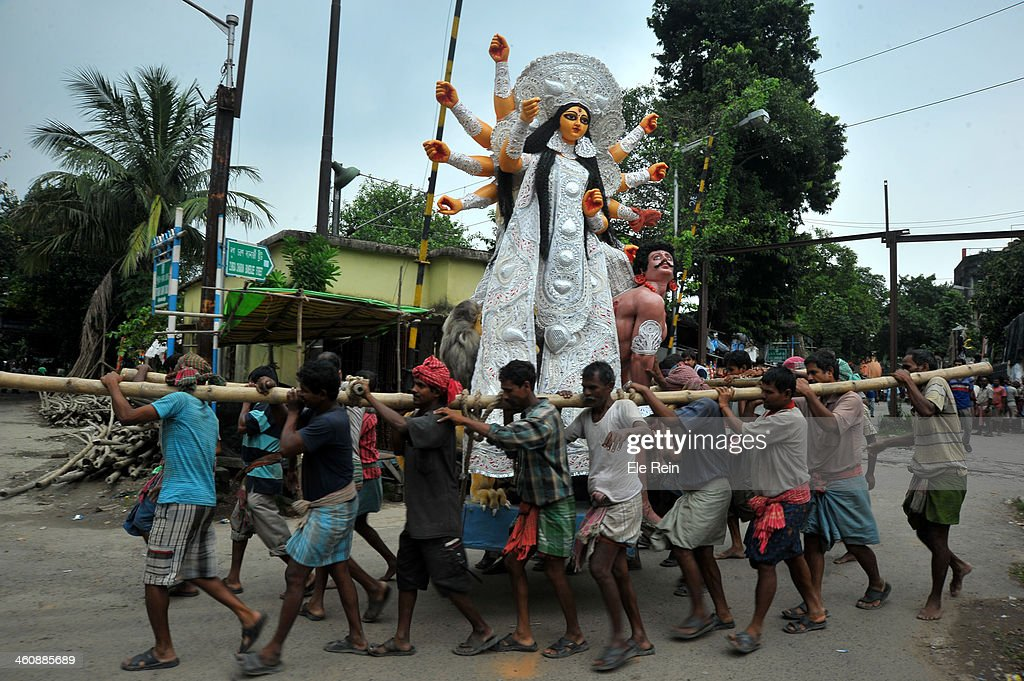 CONTENT] Clay idol of goddess Durga moving away by the artisans of Kumortuli to the place of worship