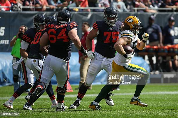 Clay Matthews of the Green Bay Packers carries the football past Kyle Long of the Chicago Bears after making an interception in the fourth quarter at...