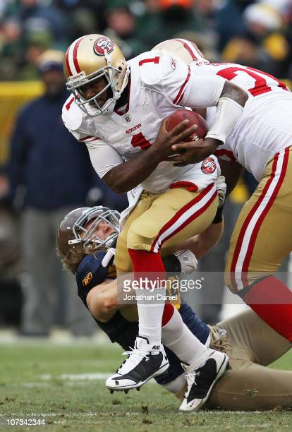 Clay Matthews of the Green Bay Packers grabs the leg of Troy Smith of the San Francisco 49ers in an effort to bring him down at Lambeau Field on...