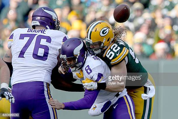 Clay Matthews of the Green Bay Packers sacks Sam Bradford of the Minnesota Vikings in the second quarter at Lambeau Field on December 24 2016 in...