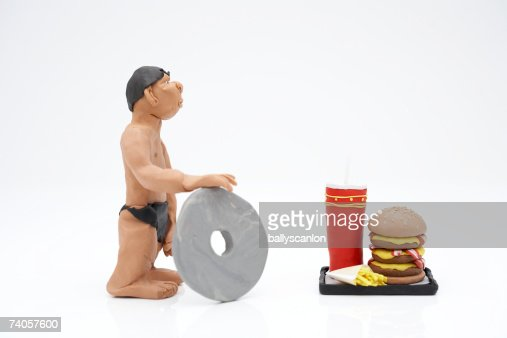 Clay Model Of Caveman And Wheel Next To Fast Food Meal On
