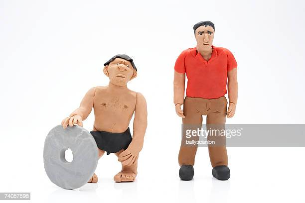 clay model of caveman with stone wheel next to modern man, on white background - caveman stock photos and pictures