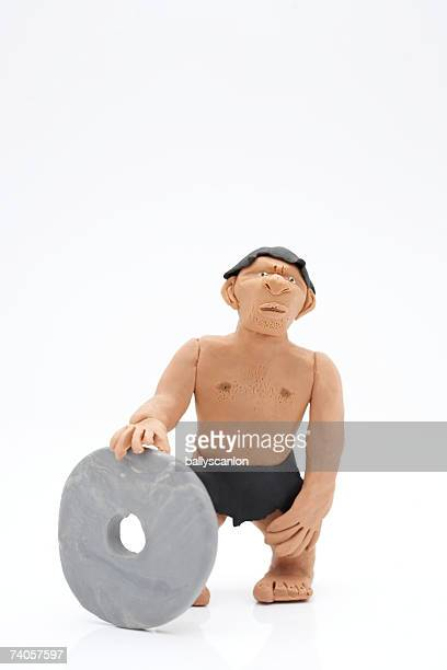 clay model of caveman with stone wheel on white background - caveman stock photos and pictures