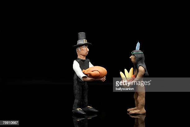 Clay model of Pilgrim and Native American Indian figures with a turkey and bowl of corn