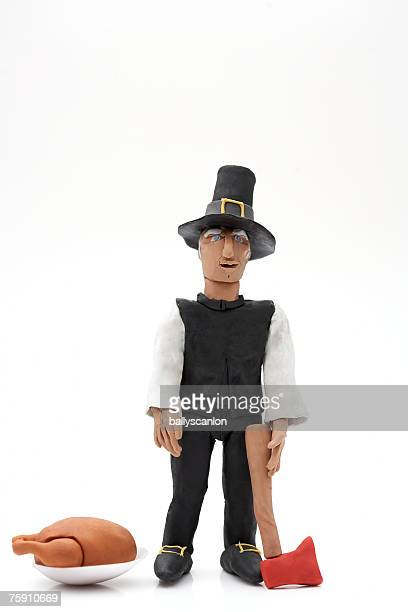 clay model of pilgrim figure with turkey and axe on a white background - pilgrims stock photos and pictures