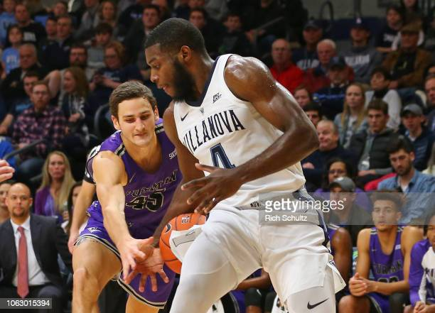 Clay Mounce of the Furman Paladins attempts to strip the ball away from Eric Paschall of the Villanova Wildcats during the first half of a game at...