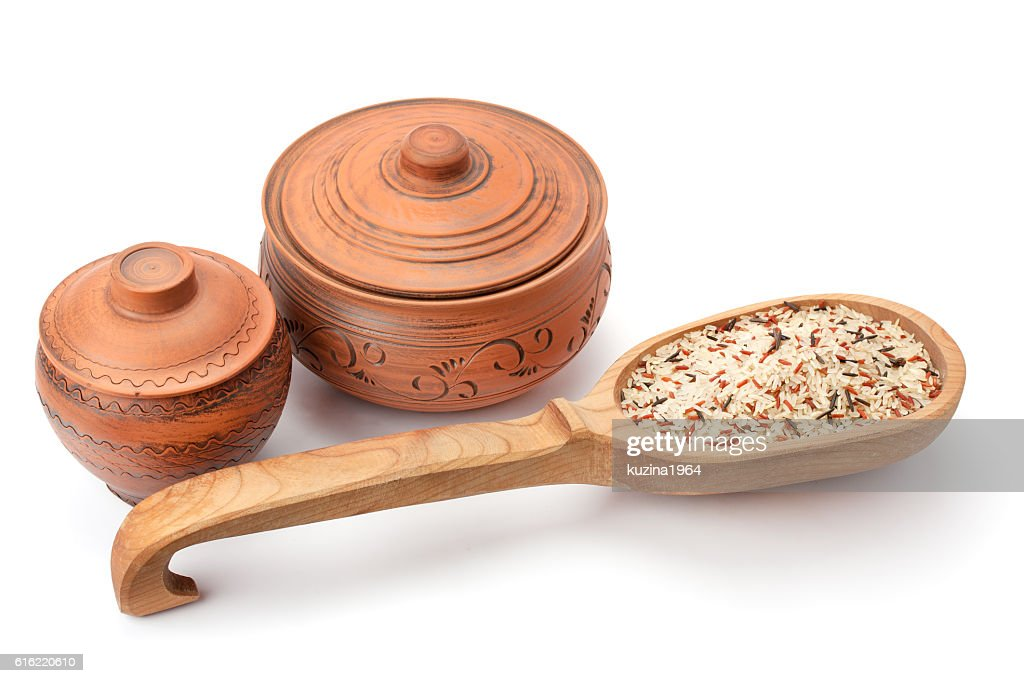 clay pots, wooden spoon and rice : Stock Photo