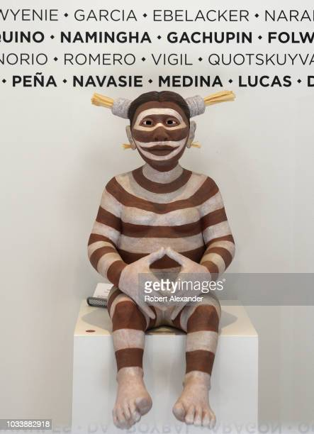 Clay sculpture of a Native American koshari, or clown figure, featured in the window display of a gallery in Santa Fe, New Mexico, which features...