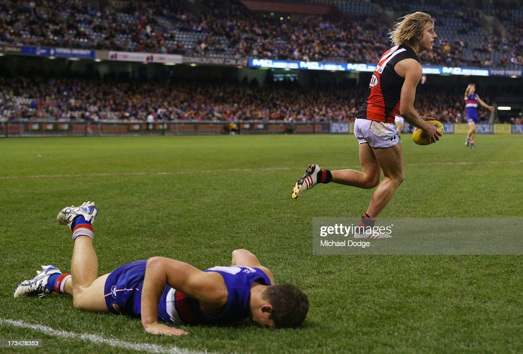 Clay Smith of the Bulldogs lies on the ground after he sustained a knee injury from the contest with Dyson Heppell of the Bombers who marked the ball in the dying stages during the round 16 AFL match between the Western Bulldogs and the Essendon Bombers at Etihad Stadium on July 14, 2013 in Melbourne, Australia.