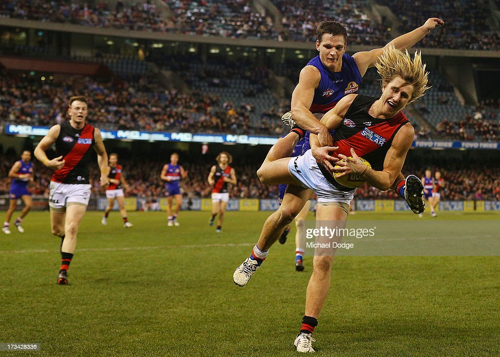 Clay Smith of the Bulldogs sustained a knee injury from this contest with Dyson Heppell of the Bombers who marked the ball in the dying stages during the round 16 AFL match between the Western Bulldogs and the Essendon Bombers at Etihad Stadium on July 14, 2013 in Melbourne, Australia.