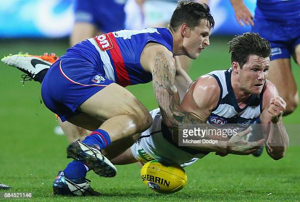 Clay Smith of the Bulldogs tackles Patrick Dangerfield of the Cats during the round 19 AFL match between the Geelong Cats and the Western Bulldogs at...