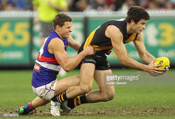 Clay Smith of the Bulldogs tackles Trent Cotchin of the Tigers during the round 20 AFL match between the Richmond Tigers and the Western Bulldogs at...