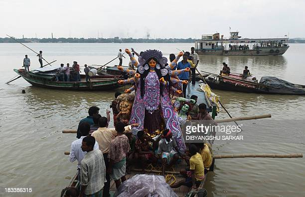 A clay statue of the Indian Hindu goddess Durga is transported from a workshop in Kumartoli the idol makers' village by boat on the river Ganges to a...