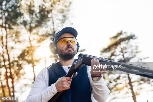 clay target shooter in sunset - shotgun stock pictures, royalty-free photos & images