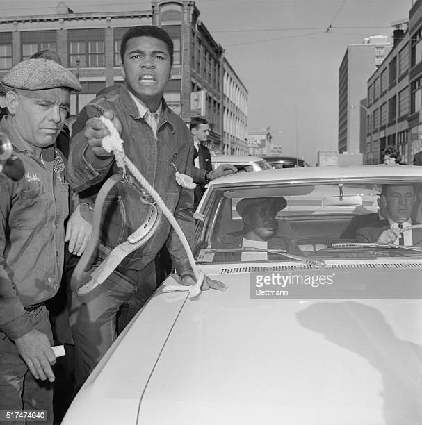 Clay taunts Liston who sits in car unperturbed as heavyweight champion Cassius Clay runs alongside moving car, shouting for that big bear and...