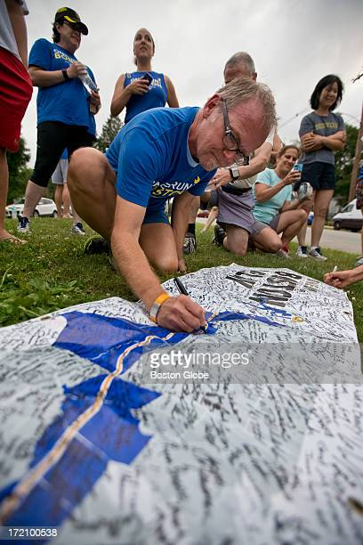 Clay Van Battenburg, from Berkeley, Calif., signs a banner at the starting line of the Boston Marathon. Van Battenburg ran 11.5 miles through the...