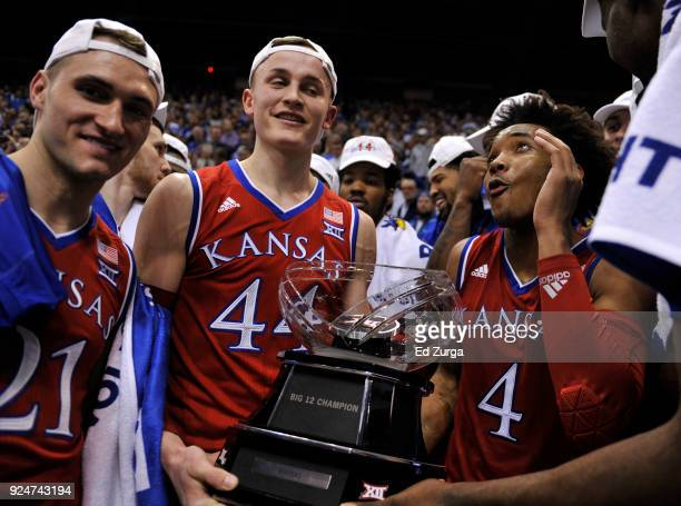 Clay Young Mitch Lightfoot and Devonte' Graham of the Kansas Jayhawks celebrate with the Big 12 Conference Trophy after their 8070 win over the Texas...