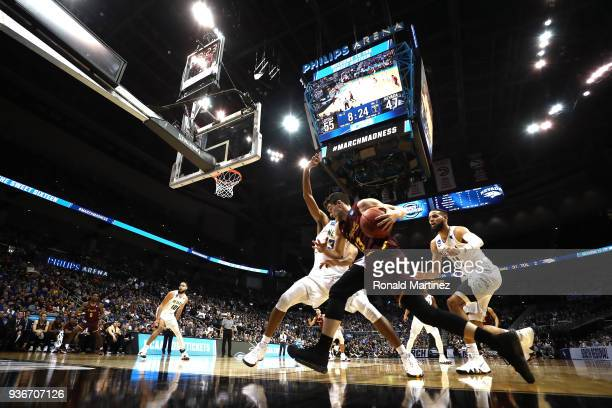 Clayton Custer of the Loyola Ramblers handles the ball against Josh Hall and Cody Martin of the Nevada Wolf Pack in the second half during the 2018...