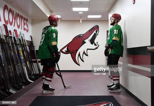 Clayton Keller and Derek Stepan of the Arizona Coyotes wear special green warm up jerseys in recognition of St Patricks Day prior to a game against...
