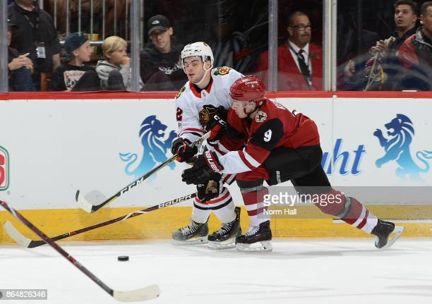 Clayton Keller of the Arizona Coyotes and Alex DeBrincat of the Chicago Blackhawks battle for a loose puck along the boards during the second period...