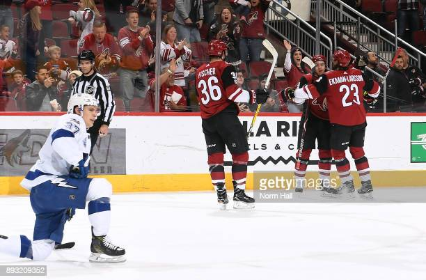 Clayton Keller of the Arizona Coyotes celebrates with teammates Oliver EkmanLarsson and Christian Fischer after his goal as Yanni Gourde of the Tampa...