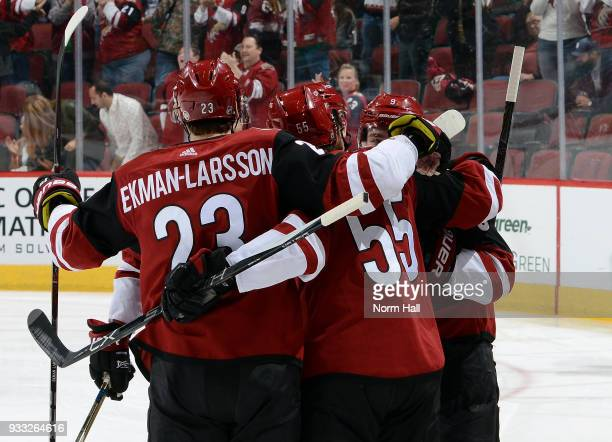 Clayton Keller of the Arizona Coyotes celebrates with teammates Oliver EkmanLarsson and Jason Demers after scoring a goal against the Minnesota Wild...