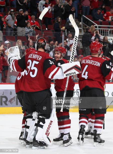 Clayton Keller of the Arizona Coyotes congratulates goaltender Darcy Kuemper after defeating the Calgary Flames in the NHL game at Gila River Arena...