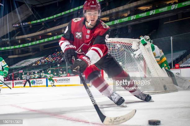 Clayton Keller of the Arizona Coyotes handles the puck against the Minnesota Wild during the game at the Xcel Energy Center on March 12, 2021 in...