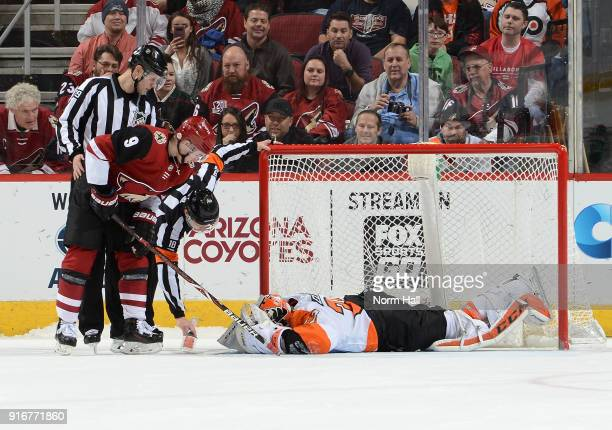 Clayton Keller of the Arizona Coyotes referee Tom Chmielewski and linesman Kiel Murchison check to see if goaltender Brian Elliott of the...