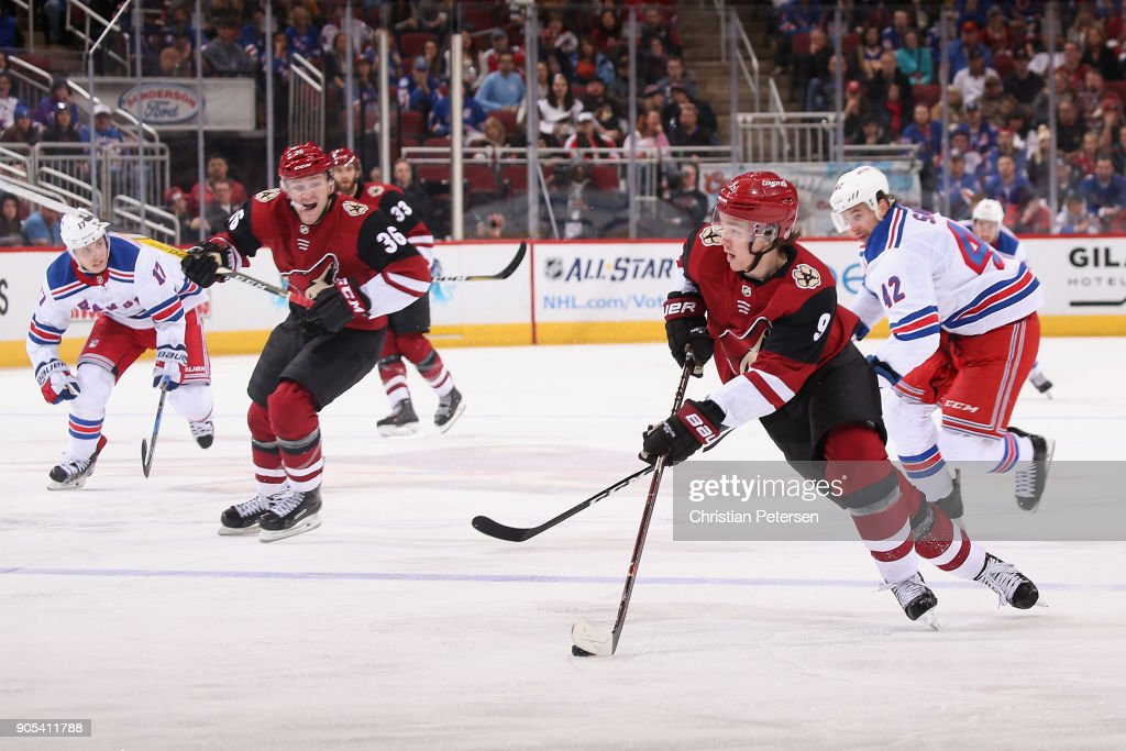 Clayton Keller #9 of the Arizona Coyotes skates with the puck ahead of Brendan Smith #42 of the New York Rangers during the thrid period of the NHL game at Gila River Arena on January 6, 2018 in Glendale, Arizona. The Rangers defeated the Coyotes 2-1 in an overtime shootout.