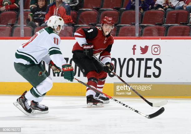 Clayton Keller of the Arizona Coyotes skates with the puck ahead of Zach Parise of the Minnesota Wild during the first period at Gila River Arena on...