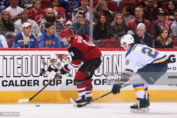 Clayton Keller of the Arizona Coyotes skates with the puck ahead of Vince Dunn of the St Louis Blues during the first period of the NHL game at Gila...